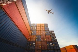 Aeroplane flying over shipping containers
